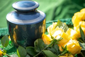 Close,Up,On,A,Burial,Urn,With,Yellow,Roses,,In